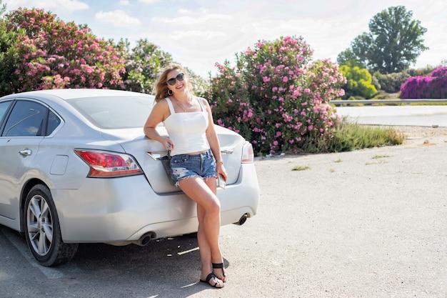 Счастливая девушка в шортах и белой футболке стоит возле машины.