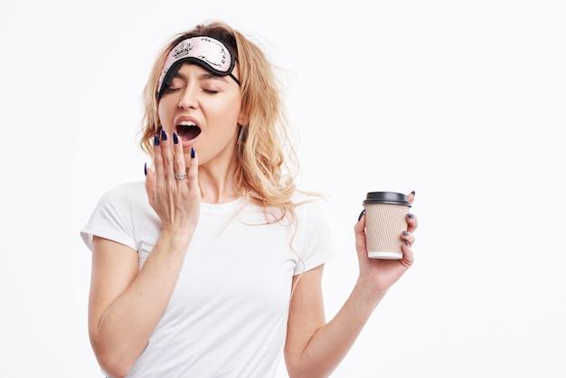 Счастливая девушка в маске сна и белой пижаме проснулась рано утром и смотрит в камеру и улыбается.