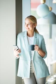 Счастливая девушка в элегантном повседневном стиле смотрит в окно, отдыхая в кафе, выпивая и используя смартфон