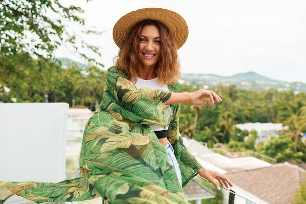 Счастливая девушка в соломенной шляпе, танцевать и веселиться на террасе.