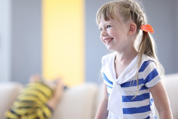 Счастливая девушка в полосатой футболке и с косичками смеется