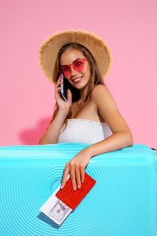 Счастливая девушка в летней одежде с багажом держит деньги на билет на паспорт во время разговора по телефону