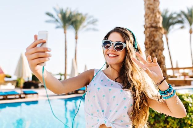 Счастливая девушка в солнцезащитных очках с загорелой кожей делает селфи со знаком мира на фоне пальм