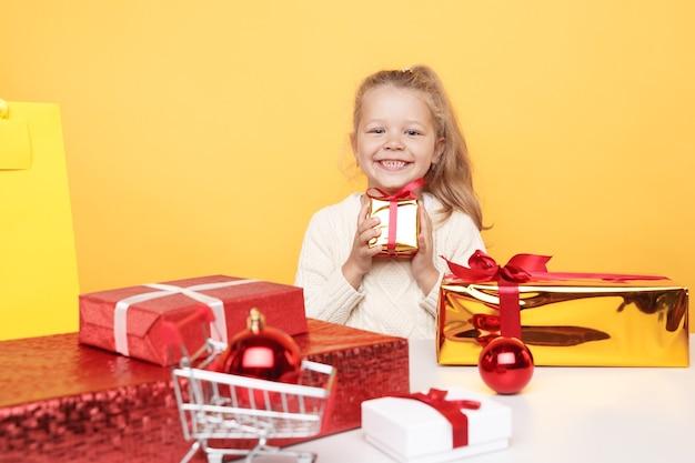 黄色の部屋に隔離された贈り物と一緒に座っているセーターの幸せな女の子。クリスマスのコンセプト。