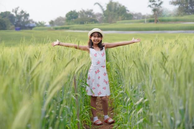 大麦畑の幸せな女の子成長する緑