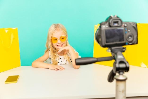 Счастливая девушка в голубой студии, выступая перед камерой для видеоблога. работаю блоггером, записываю видеоурок для интернета.