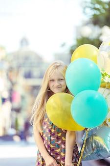 青い空と緑の牧草地を背景に、色とりどりの風船でトスカーナの牧草地で幸せな女の子。イタリア、トスカーナ