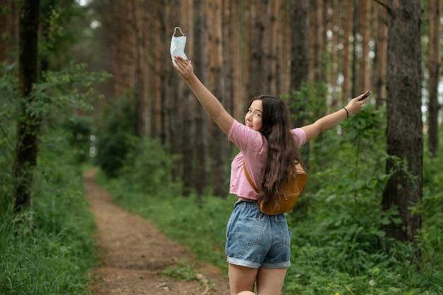 ピンクのtシャツとバックパックを背負って森の中を歩いている幸せな女の子。医療用マスクのない女の子は、新鮮できれいな空気を楽しんでいます。
