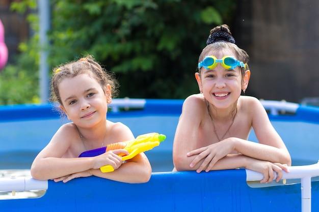 Счастливая девушка в бассейне с плавательными очками и водяным пистолетом.
