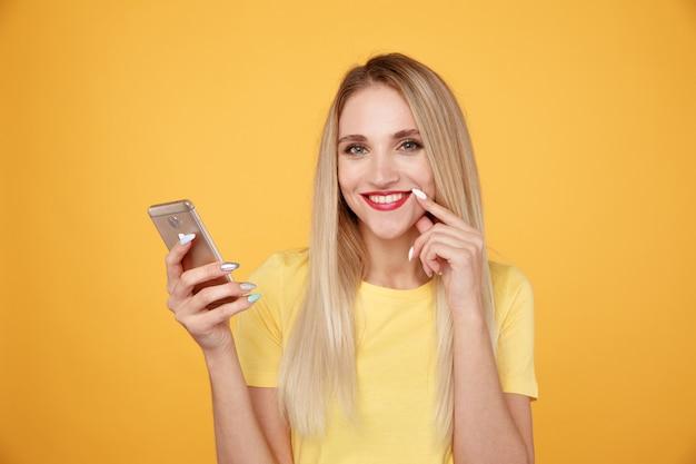 分離された電話で黄色いスタジオで幸せな女の子。