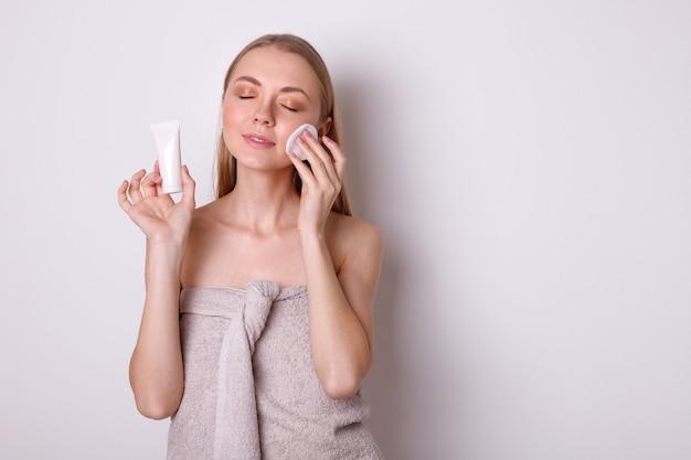 タオルで幸せな女の子はコットンパッドで顔をきれいにします