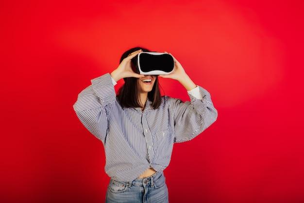 バーチャルリアリティメガネで幸せな女の子。彼女はスタジオの赤い表面に立っており、vrメガネの使用経験を積んでいます。
