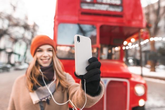 빨간 버스의 배경에 거리에 서있는 따뜻한 옷을 입은 행복한 소녀와 스마트 폰에서 셀카 찍기