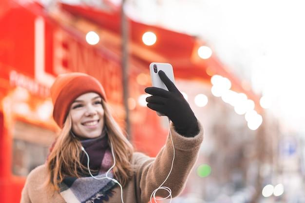 Счастливая девушка в теплой одежде стоит на улице на фоне красного автобуса и делает селфи на смартфоне