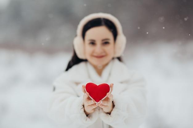 雪の背景に赤いハートを保持している暖かい白い服を着た幸せな女の子。バレンタイン・デー。