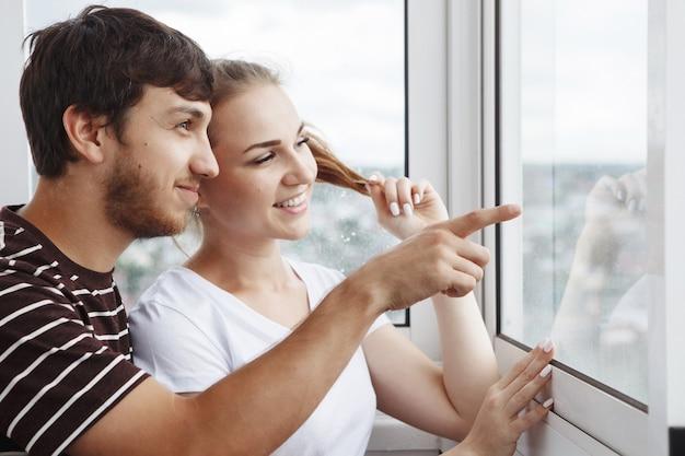 白いtシャツを着た幸せな女の子とあごひげを生やした男、新しい家の窓の外を見ているかわいいカップル