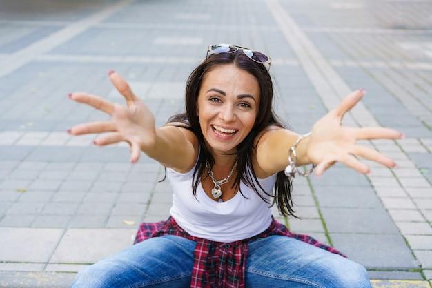白いtシャツ、ブルージーンズ、白いスニーカーの幸せな女の子は、日中公園の歩道に座っています。陽気に両手を手のひらで横に広げ、感情的な表情を浮かべる