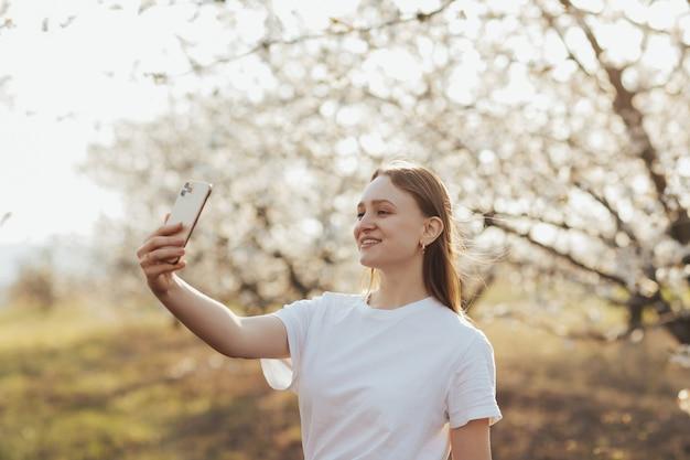 咲く木の壁に電話でselfieを取るブロンドの髪の白いtシャツの幸せな女の子。