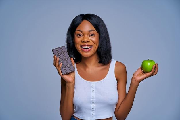 ダークミルクチョコレートバーと青リンゴを手に持って白いトップの幸せな女の子。ダイエットコンセプト