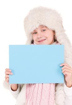 空白のボードと冬の帽子の幸せな女の子 Premium写真