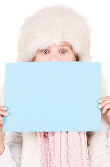 空白のボードと冬の帽子の幸せな女の子
