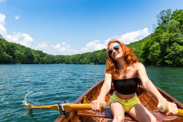 Счастливая девушка в деревянной лодке