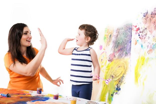 Счастливая девушка в желтой футболке и маленький мальчик в полосатой рубашке дают пять
