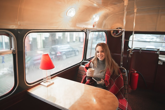 The happy girl is covered with a blanket sitting in a cafe with an original retro interior, holding a cup of coffee and a smartphone in his hands