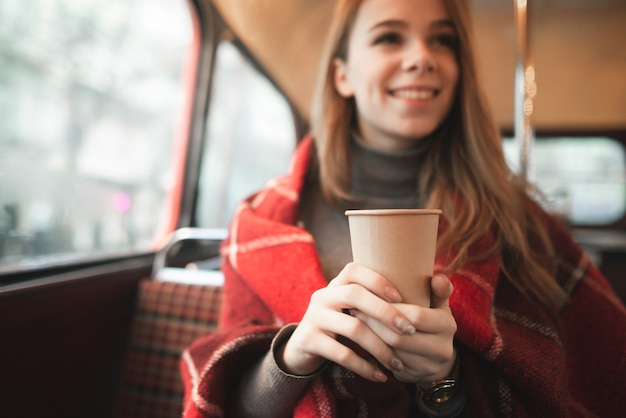 Happy girl is sitting in a cozy cafe covered with a blanket, holding a cup of coffee and warming in her hands
