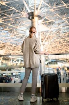 Счастливая девушка ждет вылета в аэропорту.