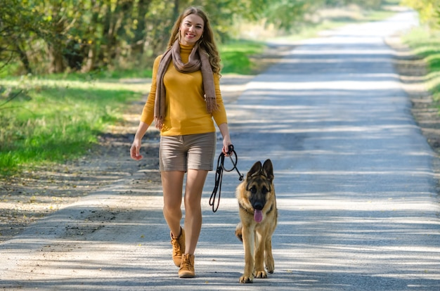 A happy girl is walking on the road in the forest with a german shepherd dog and smiling. a young teen puppy
