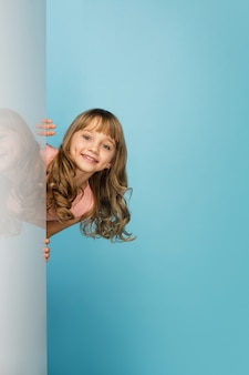 블루 스튜디오 벽에 고립 된 행복 한 여자