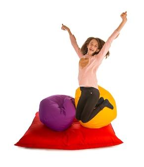 お手玉の椅子と白で隔離のお手玉のソファの近くでジャンプ幸せな女の子