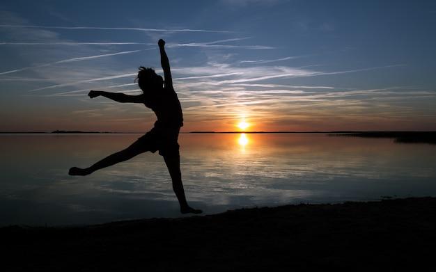 해변에서 점프하는 행복한 소녀 실루엣