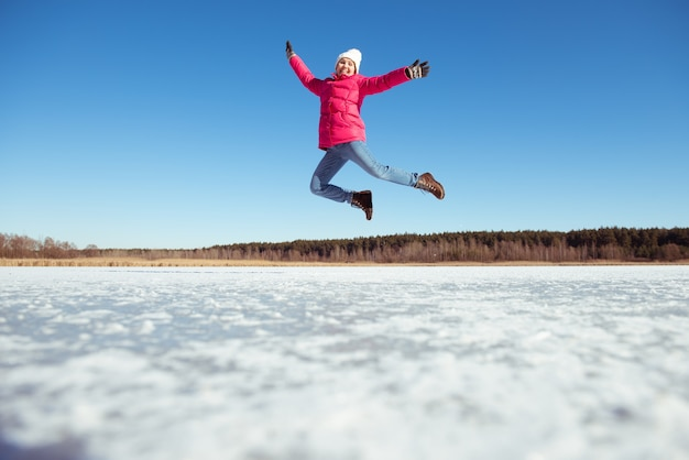青い空と雪の背景を飛び越えて幸せな女の子