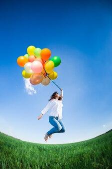 푸른 하늘에 대 한 녹색 스프링 필드에서 풍선 점프하는 행복 한 여자