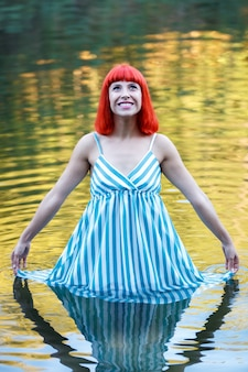 Happy girl in a lake with a blue drees