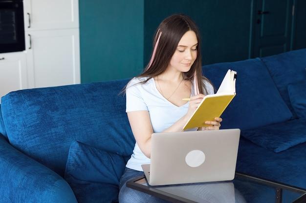 Счастливая девушка учится онлайн удаленно, используя ноутбук из дома