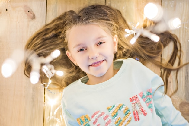 Happy girl lies on the wooden floor in her hair with a bright garland of christmas lights. smiling, looking at the camera. shooting from above, close-up portrait. copy space, new year card