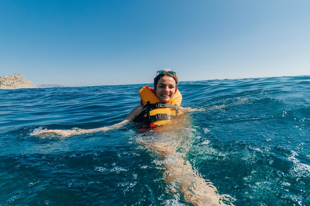 Happy girl in a life jacket swims in the water in the sea in the summer on vacation
