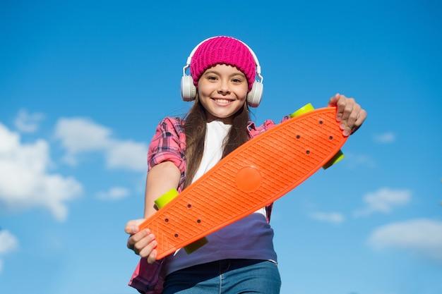행복한 소녀는 야외에서 스케이트보드 맑은 하늘, 페니 보드를 들고 현대적인 헤드폰으로 음악을 듣습니다.