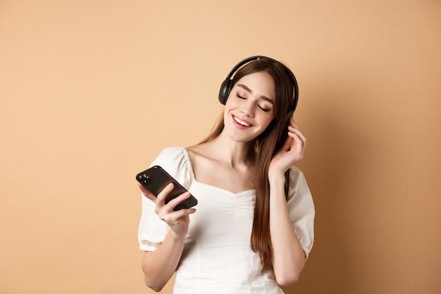 ヘッドフォンで音楽を聴いて、笑顔、スマートフォンを手に、ベージュの背景で幸せな女の子。