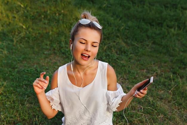 Счастливая девушка прослушивания музыки на телефоне с наушниками и знак. аудио из приложения для смартфона. молодая женщина танцует и получайте удовольствие на открытом воздухе с умным телефоном в руке.