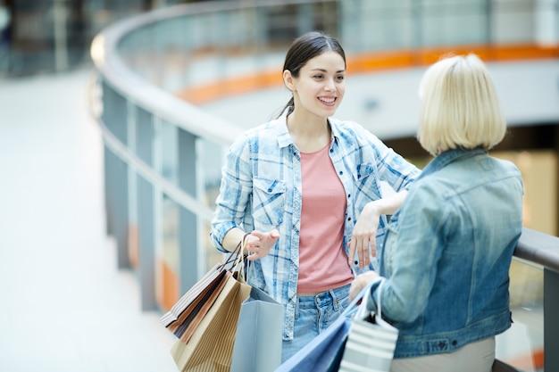 쇼핑몰의 복도에서 친구를 듣고 행복 한 여자