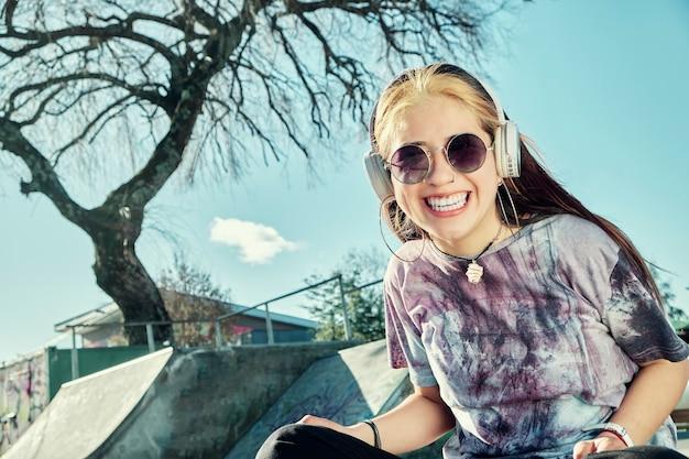 公園の椅子に座っている彼女のヘッドセットから音楽を聞いている幸せな女の子