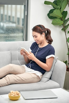 집에서 소파에 앉아 휴대폰으로 음악을 듣는 행복한 소녀