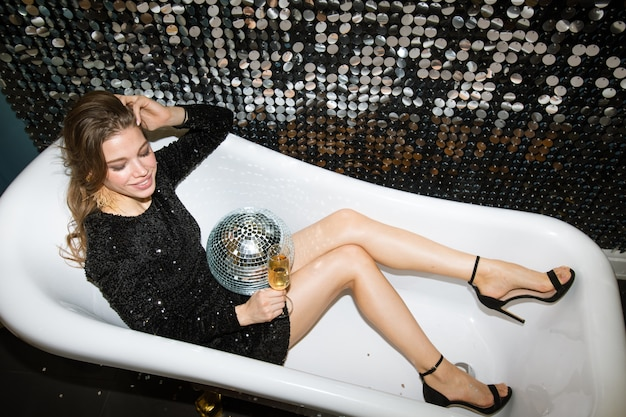 Happy girl in little black dress holding flute of champagne and disco ball while sitting in bathtub by glittering wall at party