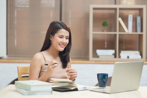 幸せな女の子がコンピューターの画面を見て、ビデオ通話でアパートでオンラインコースを聞いて学ぶ、ラップトップの概念を使用してインターネットでホームオフィスで働く若い起業家アジアのビジネスウーマン