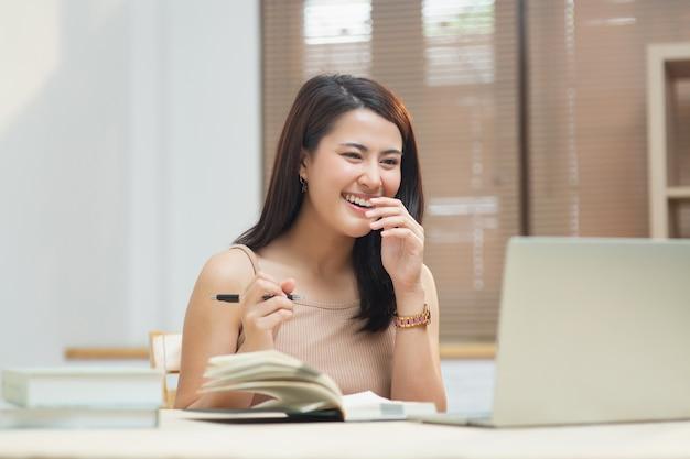 Счастливая девушка смотрит на экран компьютера, слушает и изучает онлайн-курсы в квартире с видеозвонком