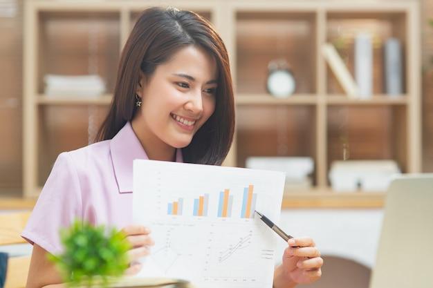 행복한 소녀는 화상 통화로 고객과 함께 노트북 화면에 그래프 결과를 보여주고, 컴퓨터를 사용하여 인터넷을 사용하여 홈 오피스에서 일하는 젊은 기업가 아시아 비즈니스 여성